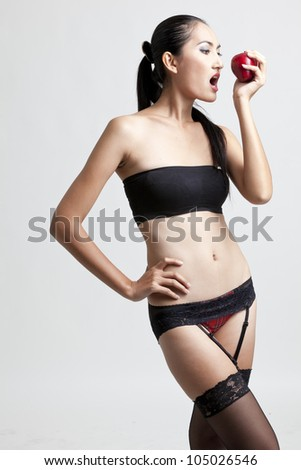 Shot of a sexy woman in black hand holding apple
