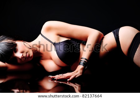 Shot of a sexy woman in black lingerie over black background. - stock photo