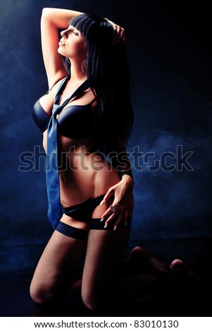 Shot of a sexy woman in black lingerie over dark background with smoke.
