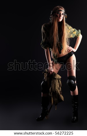 Shot of a sexy woman in military uniform posing against black background.