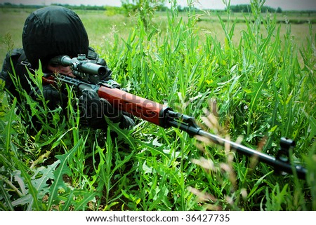 Shot of a soldier holding gun at a battlefield. - stock photo