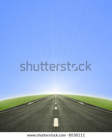 Shot of a tarmac road leading into the horizon and the sun with a blue gradient sky.
