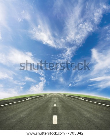 Shot of a tarmac road leading into the horizon. Beautiful blue sky and green slope beneath it.