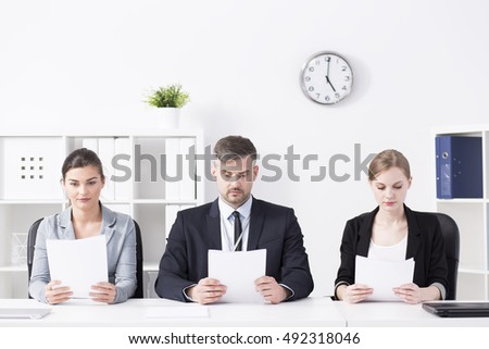 Shot of a team of professional recruiters reading CVs