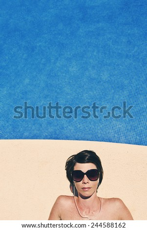 Shot of a Woman Listening to Music by the Pool - stock photo