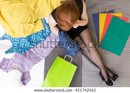Shot of a woman sitting on a bed surrounded by clothes and bags