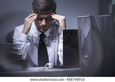 Shot of a worker having a headache in his office