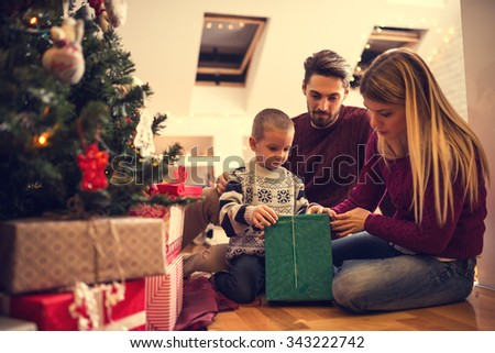 Shot of a young boy opening Christmas gift from parents. - stock photo