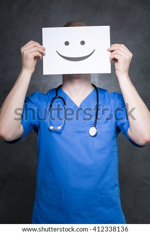 Shot of a young doctor holding a paper with a happy face on it