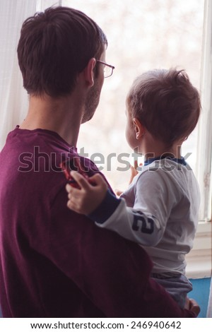 Shot of a young father standing at a window holding his adorable son - stock photo