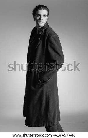 Shot of a young man in coat on light background