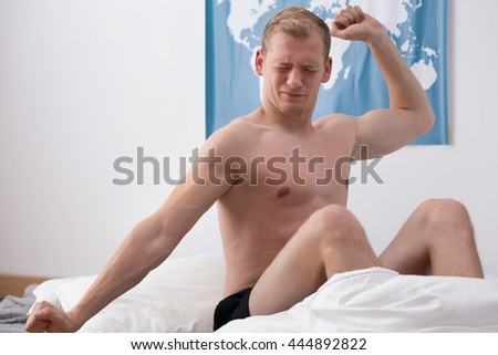 Shot of a young man sitting on a bed and stretching