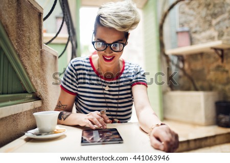 Shot of a young stylish woman using a digital tablet in a cafe  Coffee and a great book. Life's good - stock photo