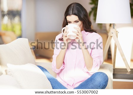 Shot of a young woman having coffee at home while sitting on couch and relaxing at home.
