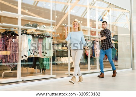 Shot of a young woman holding her credit card while her boyfriend is trying to stop her. Selective focus. - stock photo