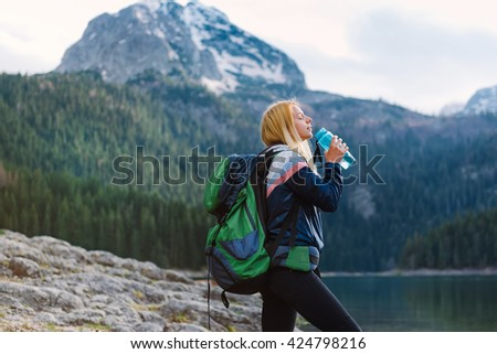 Shot of a young woman taking a water break while out hiking - stock photo