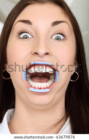 Shot of a young woman with dentists in a dental surgery. Healthcare, medicine. - stock photo