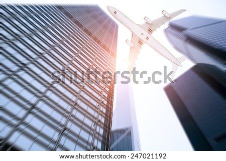 Shot of airplane flying above modern buildings - stock photo
