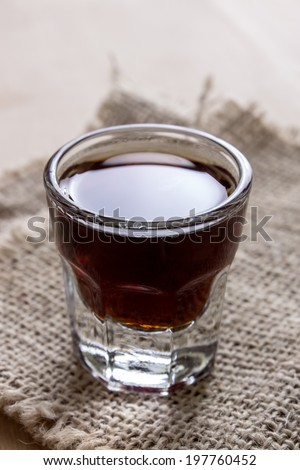 shot of alcohol on wooden table, close up photo - stock photo