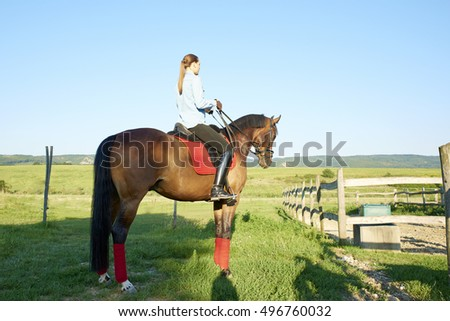 Shot of an attractive young woman on horseback at riding hall.