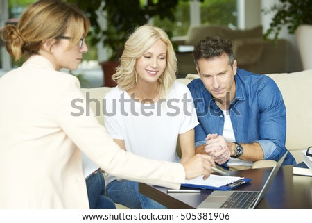 Shot of an investment advisor businesswoman consulting with middle aged couple in their home.