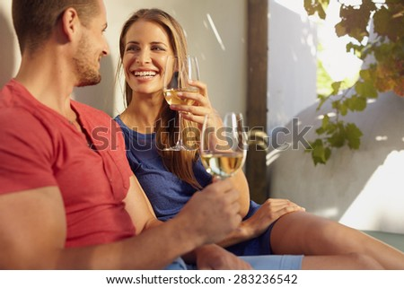 Shot of beautiful young couple enjoying a glass of white wine on an outdoor patio. - stock photo