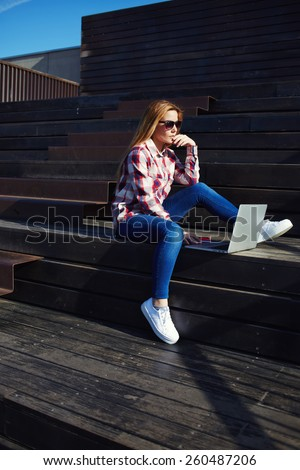 Shot of caucasian college student studying with laptop computer at campus, attractive young woman using laptop sitting on wooden staircase enjoying sunny day outdoors, charming girl - stock photo