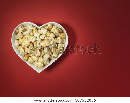 shot of cinema style popcorn in a heart shaped bowl on a bright red background with spotlit, vignette style lighting and offset with plenty of copy space for the designer.  - stock photo