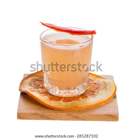 Shot of citrus liqueur with orange and chili pepper slice isolated on white background - stock photo