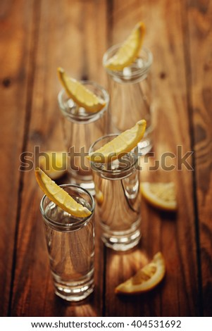 Shot of cold Vodka on rustic wooden background. Toning image. Top view. - stock photo