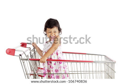Shot of cute asian girl on the shopping cart. shot in studio isolated on white - stock photo