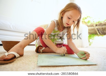Shot of cute little baby girl coloring picture while sitting on floor at home. - stock photo