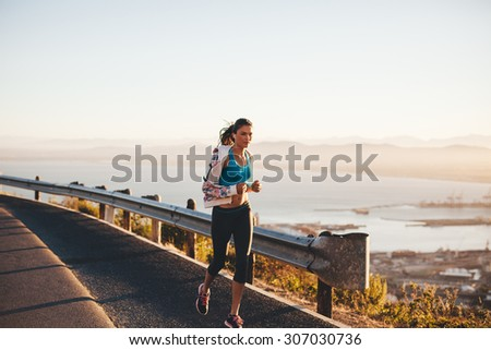 Shot of fitness woman running outdoors. Caucasian female jogging in morning on country road. - stock photo