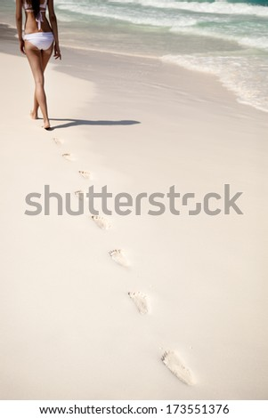 Shot of footprints with woman walks on the tropical beach - stock photo