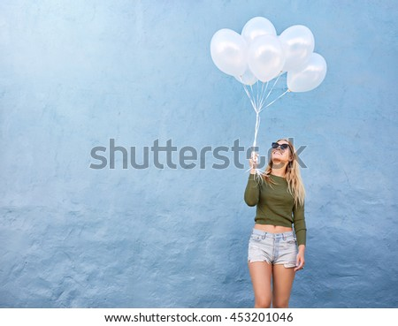 Shot of happy young woman with bunch of balloons against blue wall. Attractive female model in stylish casuals holding white balloons with copy space. - stock photo