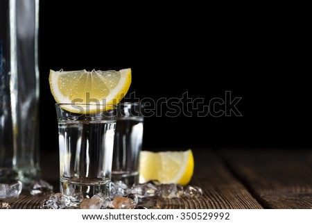 Shot of ice cold Vodka on rustic wooden background - stock photo