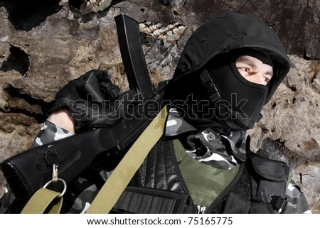 Shot of man in full ammunition holding Russian AK-47 rifle - stock photo