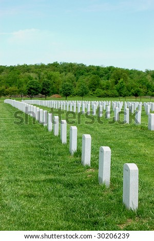 shot of military graveyard underneath a cloudy blue sky