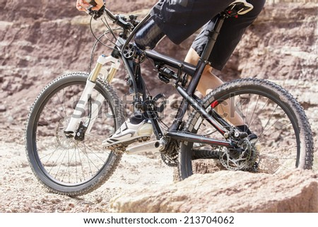 Shot of mountain bike rider with leg prosthesis between rocks.  - stock photo