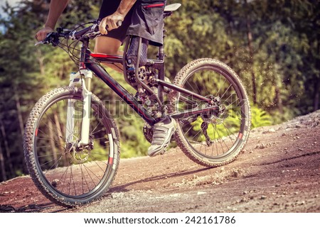 Shot of mountain bike rider with leg prosthesis riding downhill  - stock photo