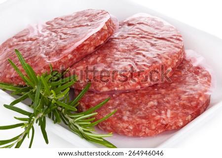 Shot of raw hamburgers with rosemary. On white tray. - stock photo