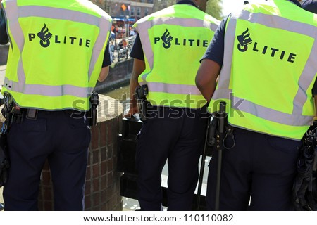 Shot of the back of police officer's jacket with the word politie written across the back on Queensday in Amsterdam - stock photo