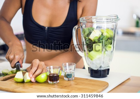 Shot of the preparation of a green detox juice. Hands of a woman cutting apple. - stock photo