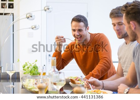Shot of three attractive men eating lunch at home. - stock photo