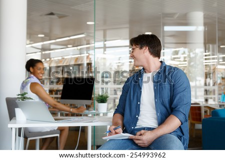 Shot of two collegues having a friendly conversation at the desk - stock photo