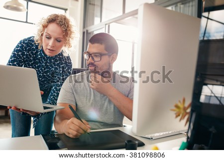 Shot of two designers working in their office using a laptop, digital graphics tablet and desktop computer. Man sitting at his desk with female colleague showing something on her laptop.