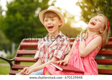 shot of two happy little kids boy and girl laughing joyfully sitting together at the park - Picture Of Little Kids