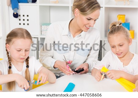 Shot of two little girls and their teacher using scissors during an art class