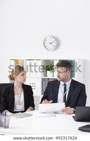 Shot of two workers talking in their office