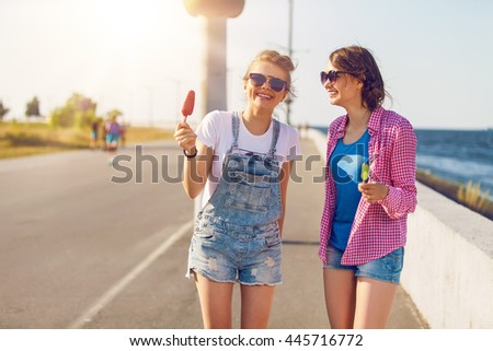 Shot of two young friends enjoying ice lollies on a summerâ??s day - stock photo